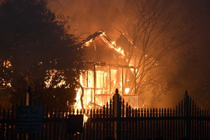 Fire engulfs the front of a house. The front fence is silhouetted by the flames.
