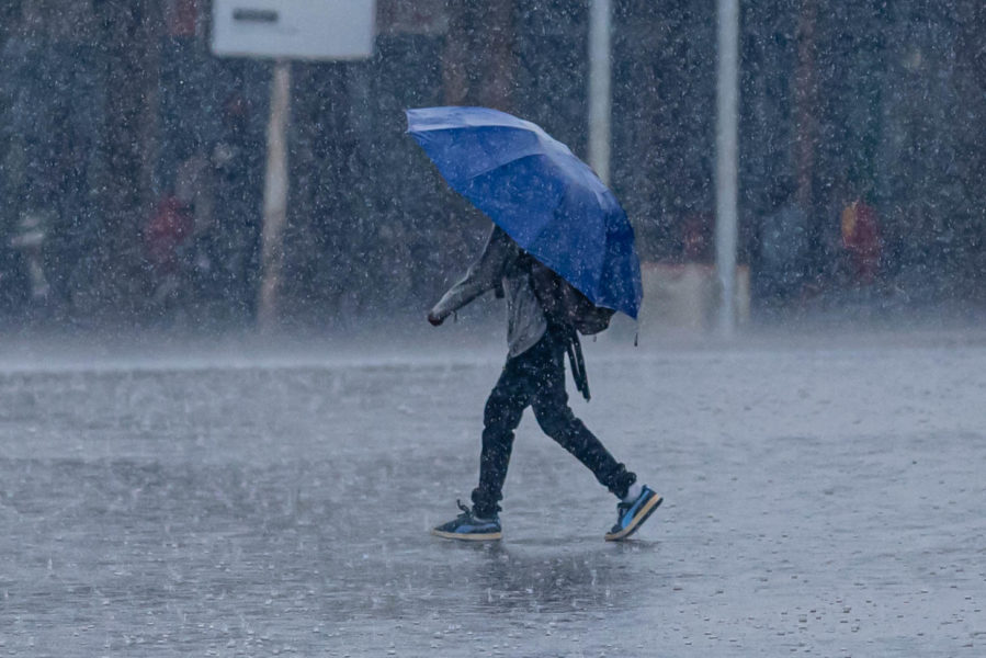 A man walks through heavy rain